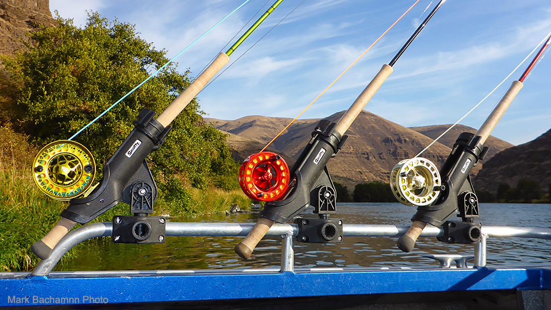 Threes Spey outfits in a jet boat rod rack, with the Deschutes River in the background.