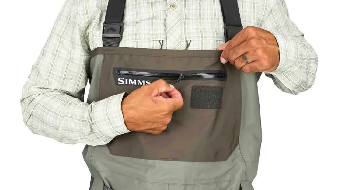 Picture: An angler showing the chest pocket feature om Simms new Freestone wader.